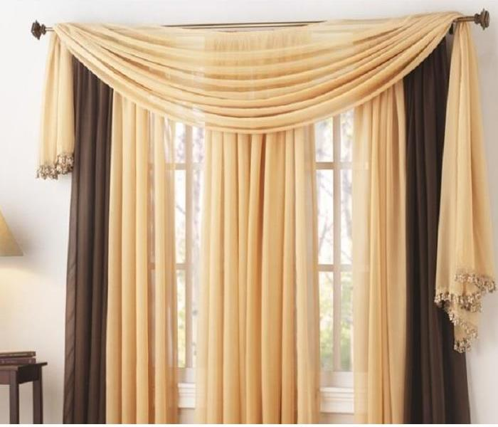 Tan and brown colored drapes hanging in front of window